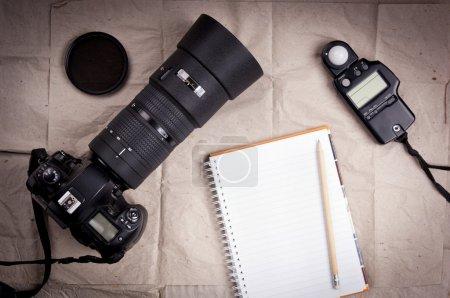 Photo pour Matériel de photographie, y compris un appareil photo reflex numérique professionnel et le posemètre un carnet vide - image libre de droit