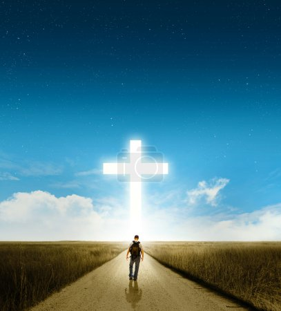 Photo for A man walking towards a large glowing Christian cross - Royalty Free Image