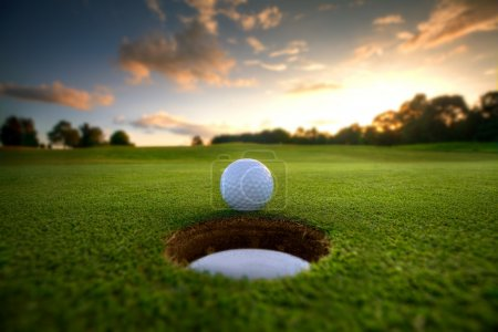 Photo for Golf ball about to fall into the cup at sunset - Royalty Free Image