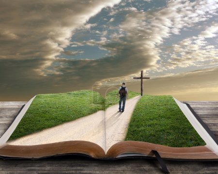 An open bible with grass and a man walking towards...