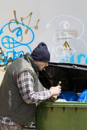 Tramp digging in dumpster