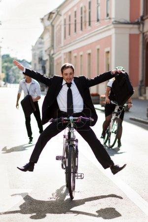 Photo pour Les hommes d'affaires en vélo et courir en ville - image libre de droit