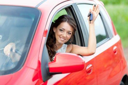 Foto de Mujer feliz en coche rojo sosteniendo las llaves y sonriendo - Imagen libre de derechos