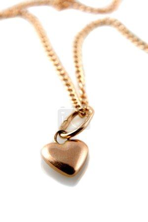 Foto de Colgante de corazón de oro rosa con cadena sobre fondo blanco - Imagen libre de derechos