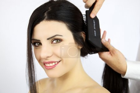 Wonderful female model getting hair brushed