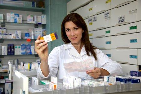 Beautiful pharmacist woman showing medicine
