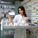 Beautiful female model pharmacist looking at medic...