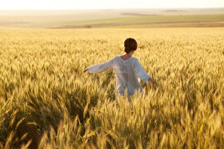 Photo for Woman in a wheat field on a summer evening - Royalty Free Image