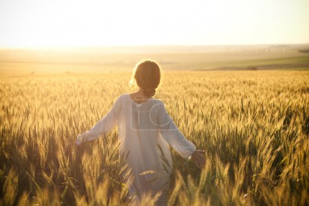 Photo for Woman in a wheat field on the background of the setting sun - Royalty Free Image