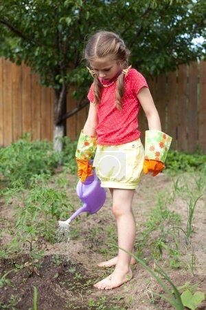 Little girl in garden gloves