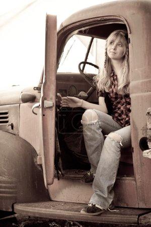 Photo pour Jolie fille blonde dans un vieux camion vintage - image libre de droit