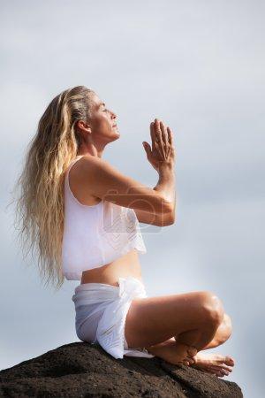 Photo pour Belle femme aux cheveux longs dans la quarantaine à hawaii en méditant sur un lit de lave - image libre de droit