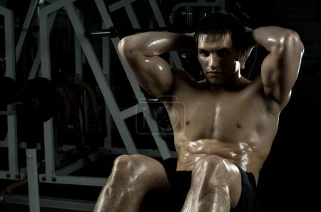 Photo for Very power athletic guy , execute exercise on muscles belly, in sport-hall, beauty glamour light - Royalty Free Image