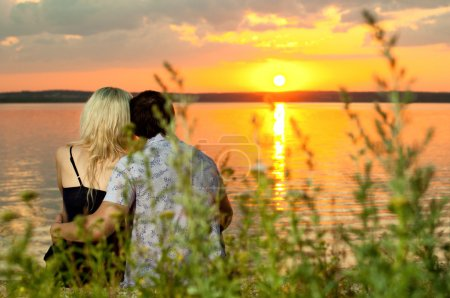 Photo pour Photo horizontale le couple heureux, en plein air sur la beauté coucher de soleil ou lever de soleil, sur la plage - image libre de droit