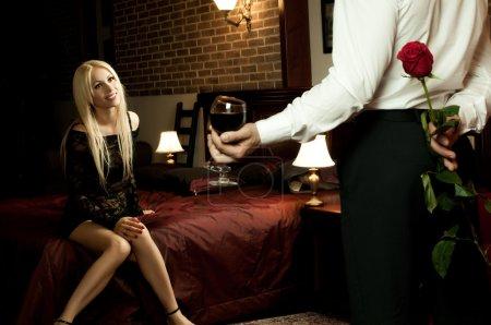 Photo pour Rendez-vous romantique en soirée dans la chambre d'hôtel, mec avec rose rouge, fille au lit sourire - image libre de droit
