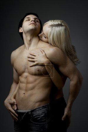 Photo pour Musculaire beau mec sexy avec jolie femme, sur fond sombre, lumière glamour - image libre de droit