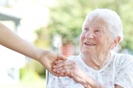 Photo for Happy senior woman holding hands with caretaker - Royalty Free Image