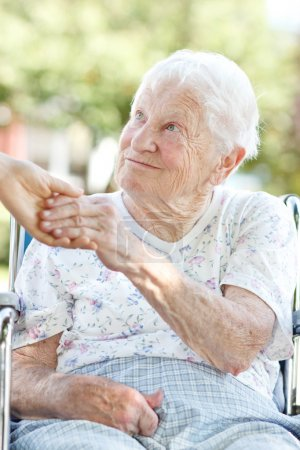 Photo for Happy senior woman holding hands with her caretaker - Royalty Free Image