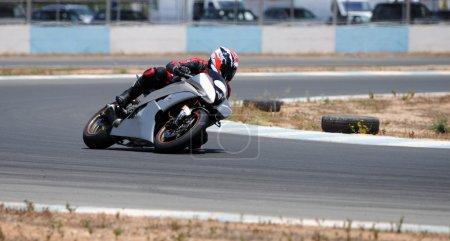 Photo pour Homme conduisant sa moto super rapide sur la piste de course lors d'une compétition de course sur route - image libre de droit