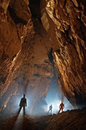 Monumental cave hall with speleologists exploring ...