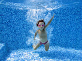 Happy underwater child jumping in swimming pool