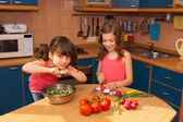 Kids cooking salad at kitchen