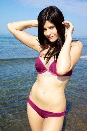Beautiful female model posing on the beach in bikini