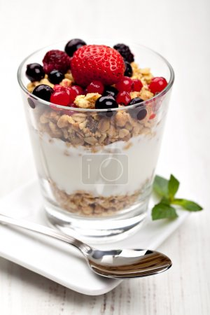 Yogurt with muesli and berries in small glass