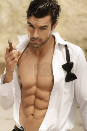 Photo for Sexy male model smoking cigar in open formal attire exposing great toned muscular body and abs - Royalty Free Image