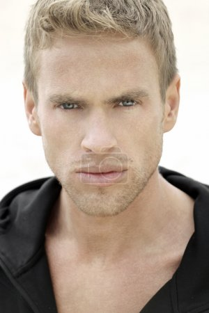 Detailed close up portrait of a young blond man...