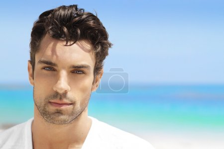 Photo for Handsome young man in casual white top against bright beach background - Royalty Free Image
