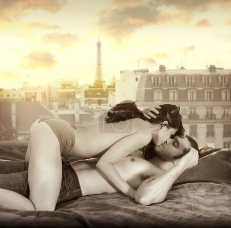 Photo for Young sexy couple making passionate love in bed against window overlooking Paris skyline with retro vintage sepia tones - Royalty Free Image