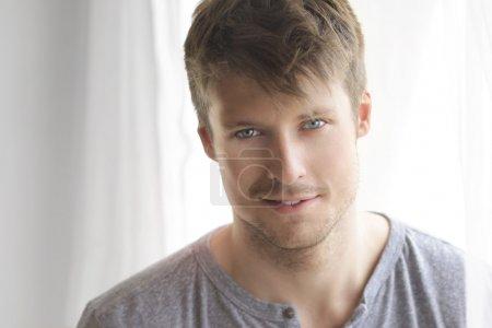 Photo pour Portrait intime d'un beau jeune homme avec joli sourire détendu et des yeux bleus étincelants près de fenêtre - image libre de droit