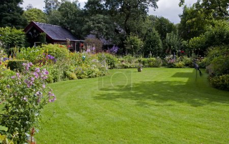 Photo pour Maison avec jardin anglais et herbe verte - image libre de droit