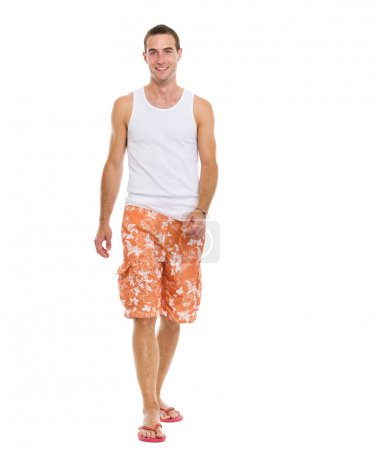 On vacation smiling young man in shorts walking
