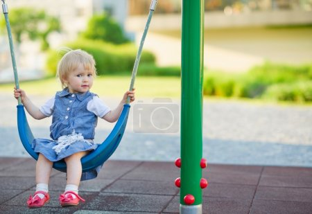 Photo pour Bébé balance sur swing sur le terrain de jeu. vue de côté - image libre de droit