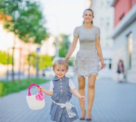 Photo pour Bébé heureux marchant avec maman en ville - image libre de droit