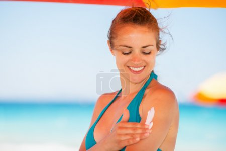 Happy woman applying sun screen creme on arm