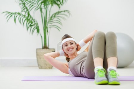 Happy healthy woman doing abdominal crunch