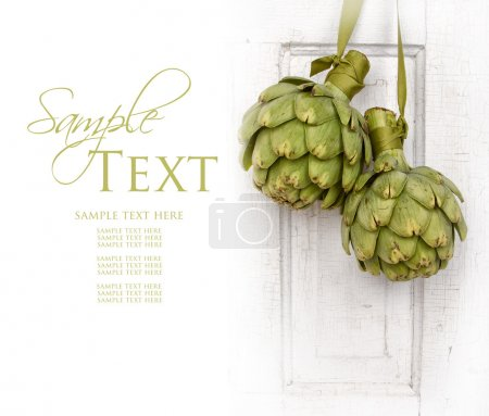 Two artichokes hanging from a vintage door