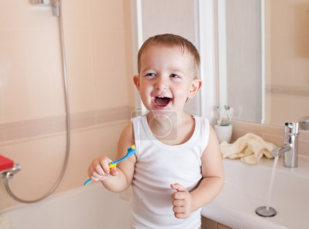 Boy brushing teeth in bathroom