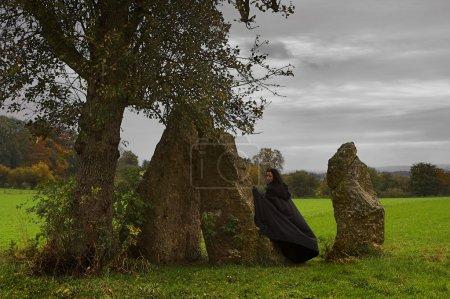 Photo pour Femme ou sorcière en cape noire marchant autour d'un groupe de menhirs et d'un arbre solitaire - image libre de droit