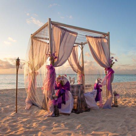 Photo pour Table de mariage romantique décoré magnifique sur la plage tropicale des Caraïbes au coucher du soleil - image libre de droit
