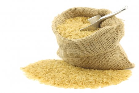 Unpolished rice (whole grain) in a burlap bag with an aluminum scoop