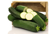 Fresh zucchini's and a cut one in a wooden box