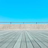 Balcony, Wood plank floor, concrete fence, blue sky. Bottom view