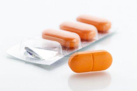 Photo pour Plaquette thermoformée de pilules orange avec extrait au premier plan - image libre de droit