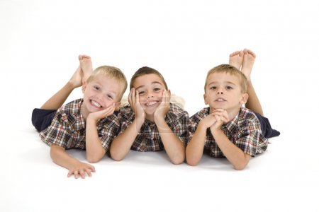Photo for Three Caucasian boys laying on a white background and smiling. - Royalty Free Image