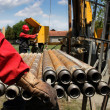Oil drilling rig workers lifting drill pipe. Focus...