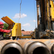 Oil drilling rig workers lifting drill pipe....